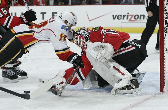 Antti Niemi makes a stop against Calgary on Monday, something Cristobal Huet couldn't do.