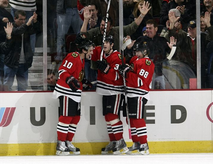 Patrick Sharp, Dave Bolland and Patrick Kane celebrate the game-winning goal.