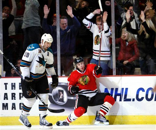 San Jose's Joe Thornton accepts defeat as Brent Seabrook celebrates his game-winning goal.